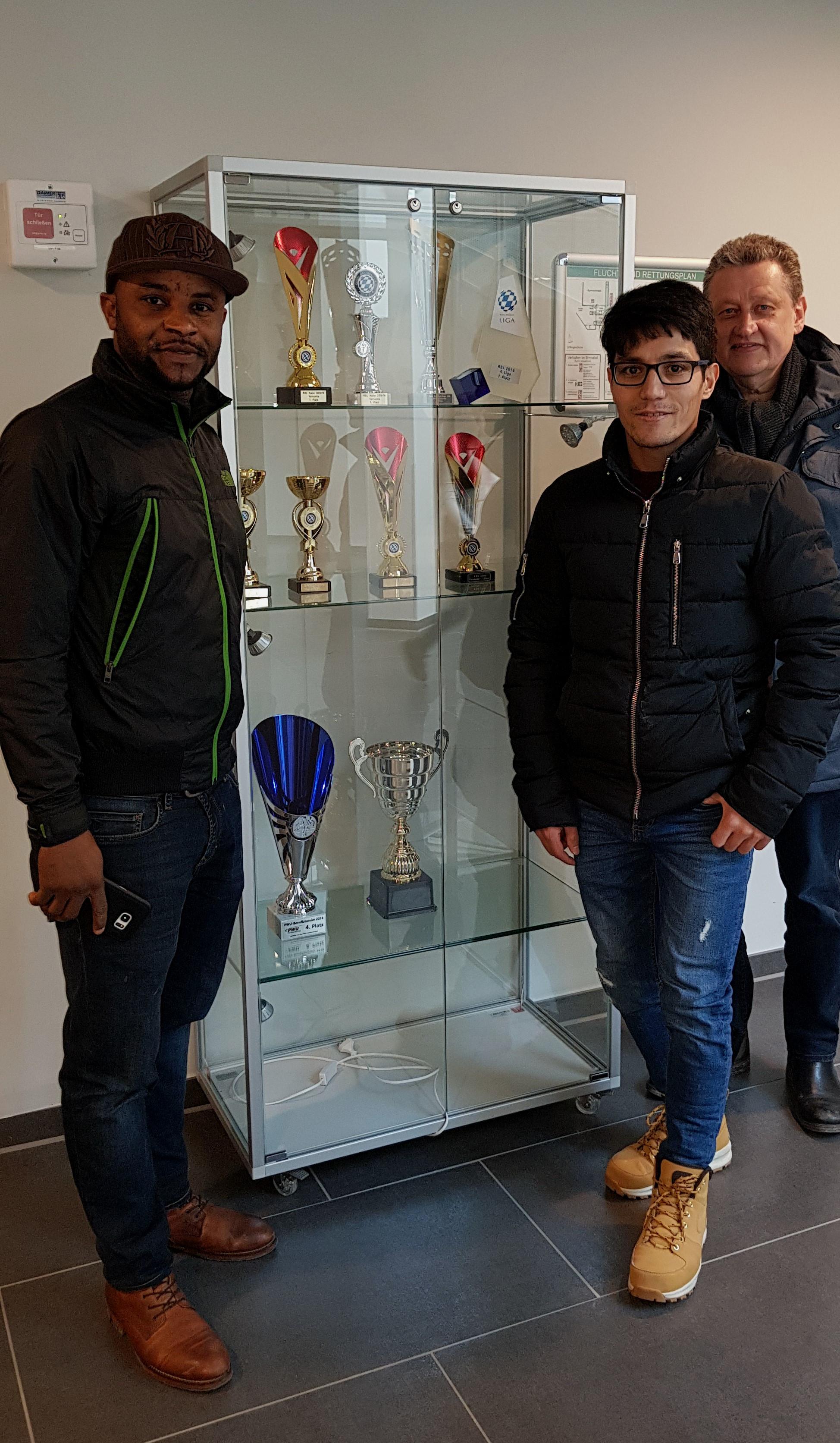 Geflüchtete Sportler zeigen Pokale im Sportzentrum